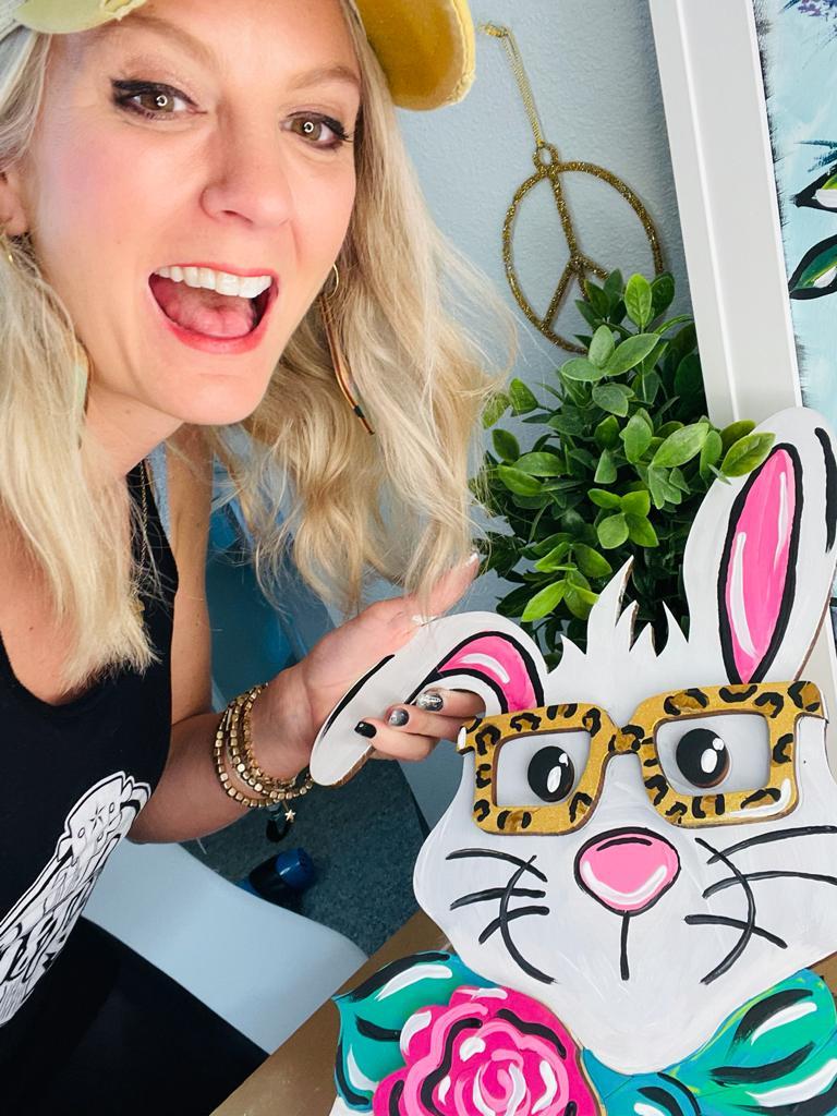 Heidi Easley holding a painted bunny door hanger