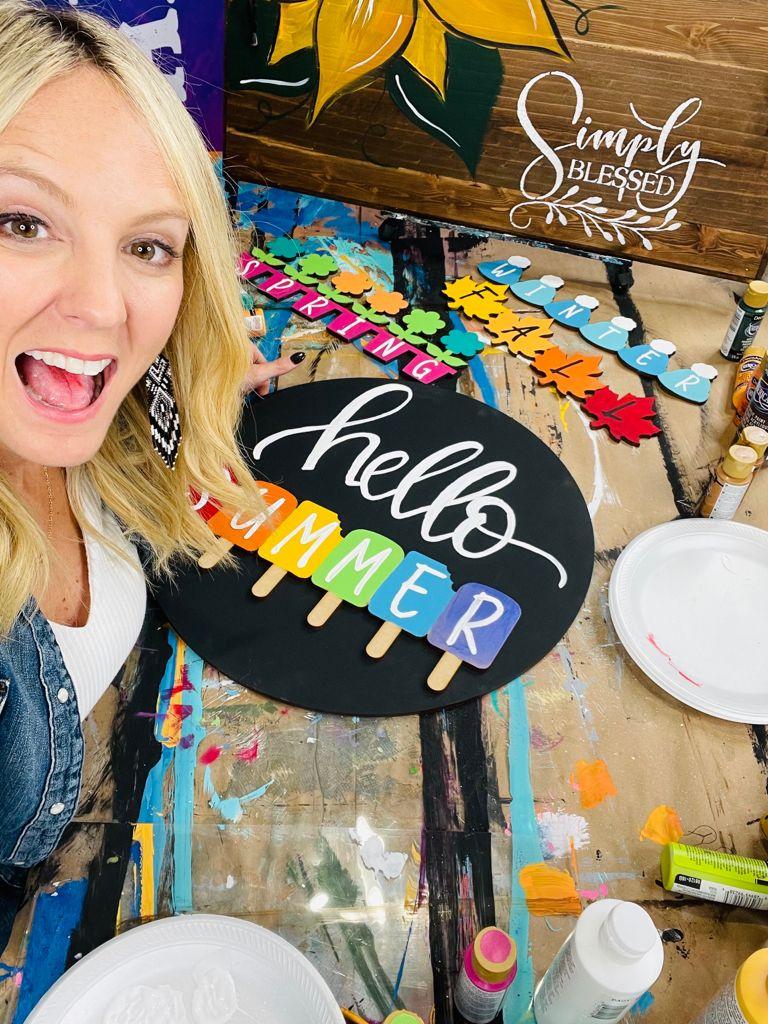 Heidi Easley with a hand painted interchangeable door hanger