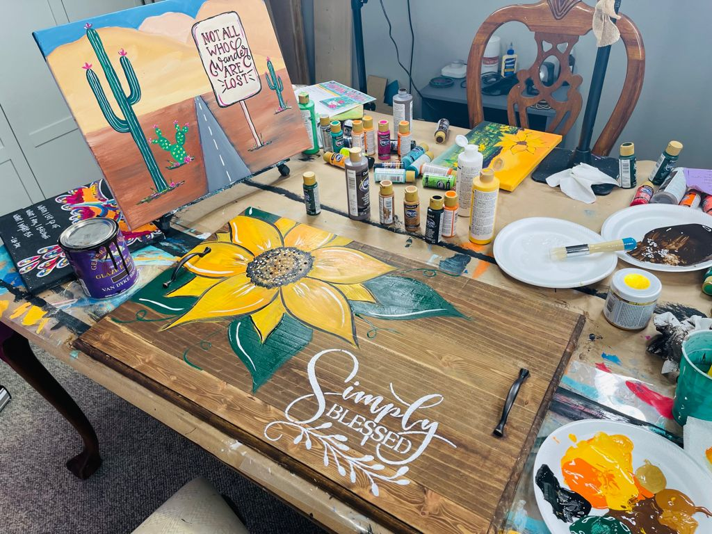 """noodle board with hand painted sunflower and stenciled words """"simply blessed"""" and bottles of acrylic paint, acrylic painting of a desert scent with words """"not all who wander are lost"""""""